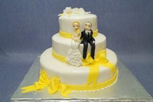 Триетажна сватбена торта с жълта панделка и захарни фигурки на младоженци