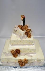 Четири етажна сватбена торта  с фондан, фигурка с младоженци и златни перли и рози